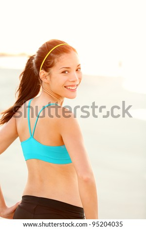 Sporty fitness woman outdoor workout. Young runner woman smiling happy resting after jogging training on beach at sunset. Beautiful mixed race Caucasian / Chinese Asian fit fitness model outside. - stock photo