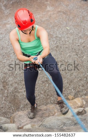 Sporty girl abseiling down rock face wearing red helmet - stock photo