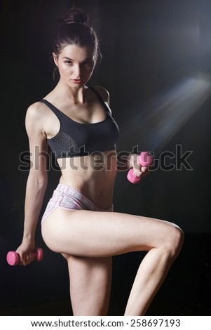 Sporty girl doing exercise with dumbbells in the gym. Attractive fitness woman, trained female body, lifestyle portrait, caucasian model. - stock photo