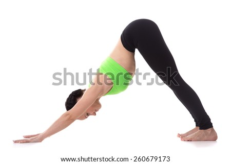 Sporty girl on white background stretching in downward-facing dog yoga pose, adho mukha svanasana, asana from Surya Namaskar sequence, Sun Salutation complex - stock photo