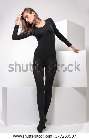 sporty girl posing in studio on large white cubes - stock photo