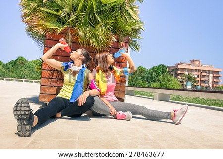 Sporty girlfriends drinking energetic juice during a break at run training in urban park area - Young happy women having fun together with fitness jogging exercise - Tilted horizon and warm color look - stock photo