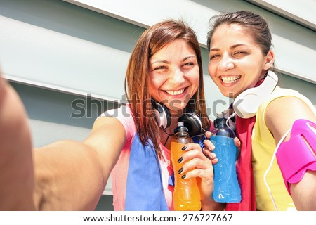 Sporty girlfriends taking phone selfie during a break at run training in urban area - Young happy women having fun together with fitness jogging workout - Fashion sport clothes and energetic drinks - stock photo