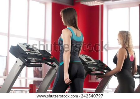 Sporty girls exercising on cardio trainer, treadmill in gym (view from the back) - stock photo