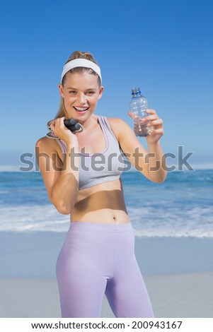 Sporty happy blonde standing on the beach with water bottle and skipping rope on a sunny day - stock photo