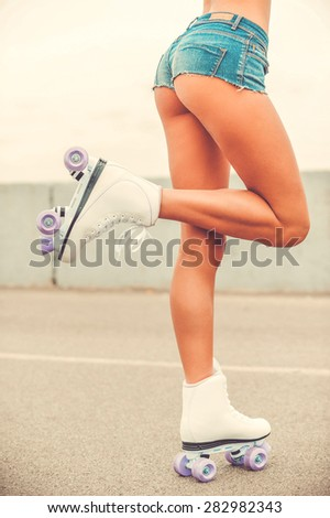 Sporty legs. Close-up of young woman with perfect buttocks wearing roller skates and lifting her leg up while standing outdoors - stock photo