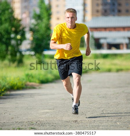 Sporty man jogging in city street park. Outdoor fitness. - stock photo