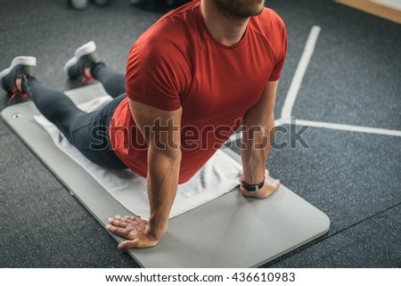 Sporty man stretching back before gym workout. Fitness strong male athlete on floor mat and towel warming up indoor. - stock photo