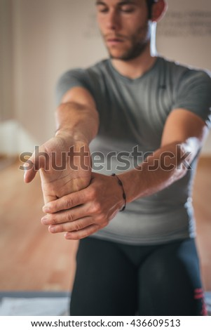 Sporty man stretching forearm before gym workout. Fitness strong male athlete standing indoor warming up. - stock photo
