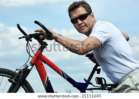 Sporty mature man cycling along cross country. - stock photo