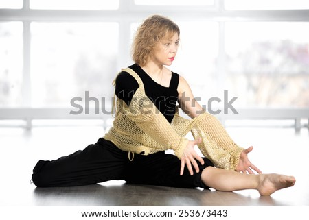Sporty mid age woman practicing yoga, doing exercises for flexibility, dancing, sitting in half-split position in class - stock photo