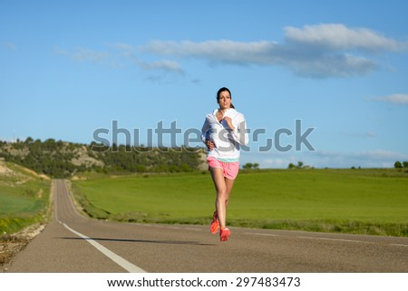 Sporty motivated woman running on country side road. Female athlete training outdoor. - stock photo