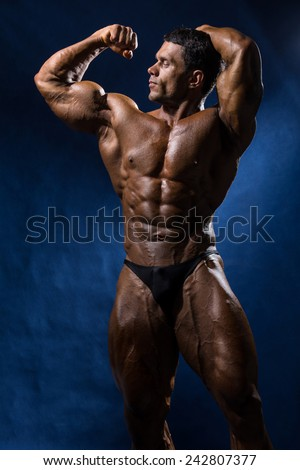 Sporty muscular man bodybuilder shows his body and strength on a blue background. - stock photo