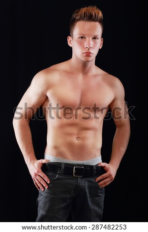 sporty muscular young man in jeans posing over dark background. - stock photo