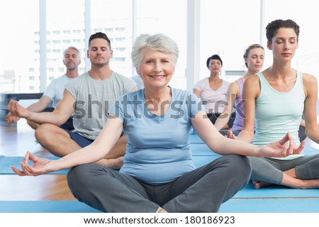 Sporty people sitting in lotus pose at a bright fitness studio - stock photo