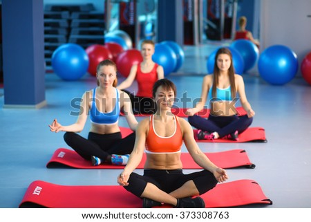 Sporty people sitting on exercise mats at a bright fitness studio - stock photo