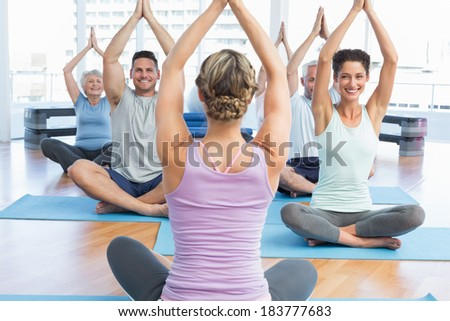 Sporty people with joined hands over heads at fitness studio - stock photo
