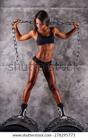Sporty sexy girl with great abdominal muscles in black sportswear. Tanned young athletic girl stands on vent pipes and holding circuit. A great sport female body. The girl athlete with muscular corpus - stock photo