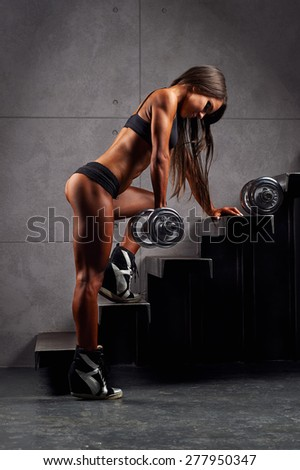 Sporty sexy girl with great abdominal muscles in black sportswear. Tanned young athletic girl with dumbbells with a nice beefy buttocks and biceps on the stairs. A great sport female body. Miss bikini - stock photo