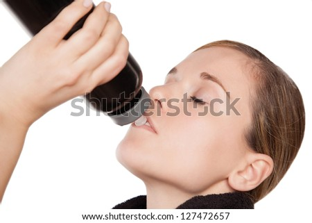 Sporty thirsty young woman drinking from a water bottle, closeup - stock photo