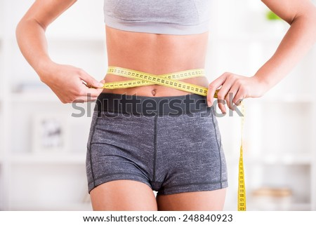 Sporty woman and measure around her body at home. - stock photo