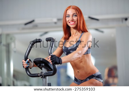 sporty woman at the gym on bike - stock photo