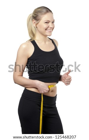 Sporty woman doing a thumbs up while holding a tape measure around her waist - stock photo