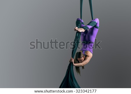 Sporty woman doing exercise with elastics, aerial silk ribbons. Sport training gym and lifestyle concept. Anti-gravity yoga. - stock photo