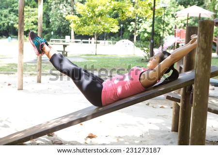 Sporty woman doing reverse crunches in outdoor park. - stock photo