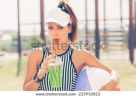 Sporty woman drinking water against the sports ground. Outdoor lifestyle portrait - stock photo