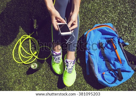Sporty woman holding phone with empty screen sitting on the green grass with jump rope, backpack and drink bottle - stock photo