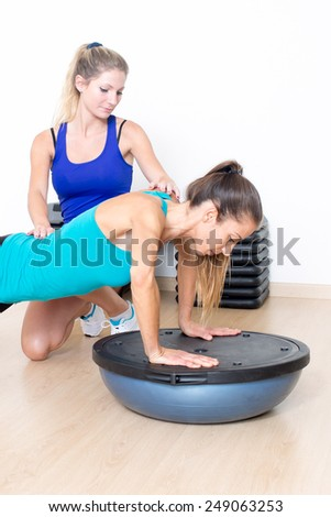 sporty woman in gym with female coach - stock photo