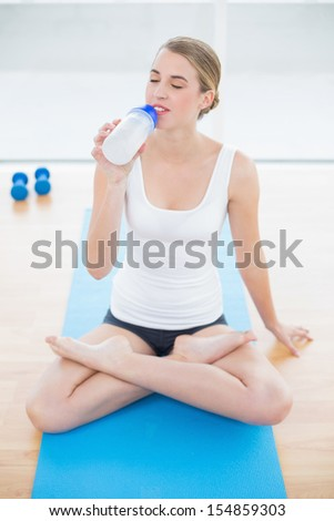 Sporty woman in lotus position in bright sports hall drinking water - stock photo
