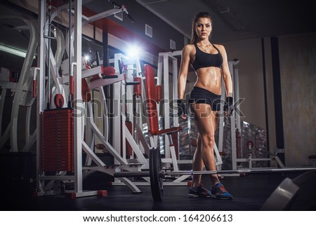 Sporty woman in the gym with exercise equipment and barbell - stock photo
