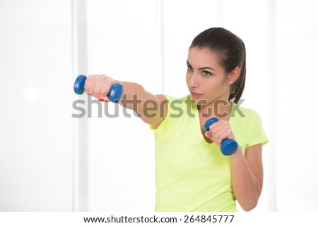 Sporty woman in yellow t-shirt attack holding in her arms dumbbells - stock photo
