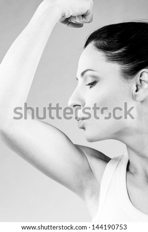 sporty woman is kissing her biceps muscle on grey background - stock photo