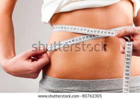 sporty woman is measuring her waist on grey background - stock photo