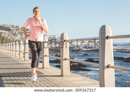 Sporty woman jogging at promenade on a sunny day - stock photo
