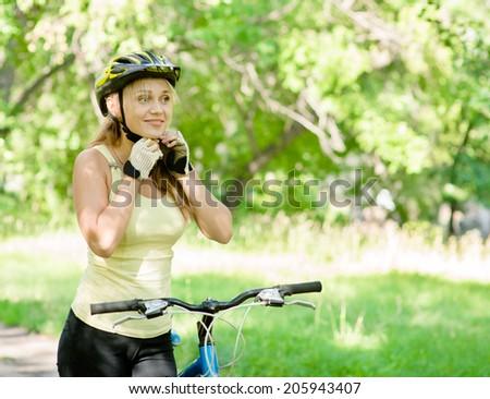sporty woman on mountain bike putting biking helmet - stock photo
