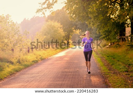 Sporty woman running on a country road beneath leafy green trees approaching the camera as she does her daily exercise and training jogging in the fresh air, low angle, view - stock photo