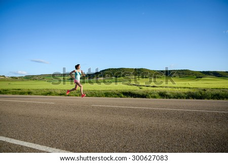Sporty woman running on country side road. Female athlete training and exercising outdoor. - stock photo