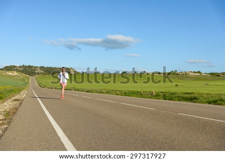 Sporty woman running on country side road. Female athlete training outdoor. - stock photo