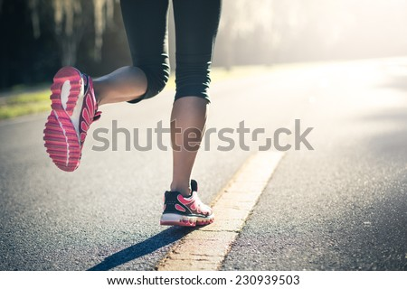 Sporty woman running on road at sunrise. Fitness and workout wellness concept.  - stock photo