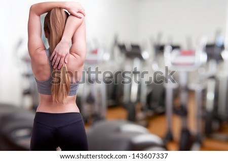 Sporty woman stretching her arm, in a gym - stock photo