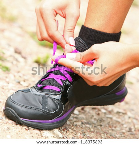 Sporty woman tying her shoelaces close up - stock photo