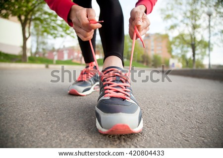 Sporty woman tying shoelace on running shoes before practice. Female athlete preparing for jogging outdoors. Runner getting ready for training. Sport active lifestyle concept. Close-up - stock photo