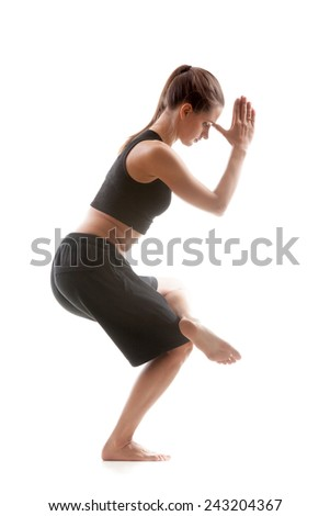 Sporty yoga girl on white background standing on one leg with palms folded in mudra - stock photo