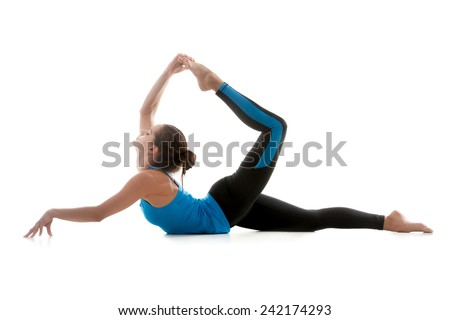 Sporty yoga girl on white background stretching her leg muscles in Upward Wheel Pose - stock photo