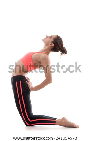 Sporty yoga girl stands on her knees on white background while stretching her back - stock photo