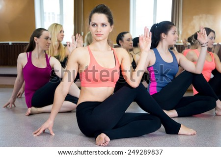 Sporty Yoga girls in class exercise sitting in Ardha Matsyendrasana (Half Lord of the Fishes Pose, Half Spinal Twist Pose or Vakrasana) - stock photo